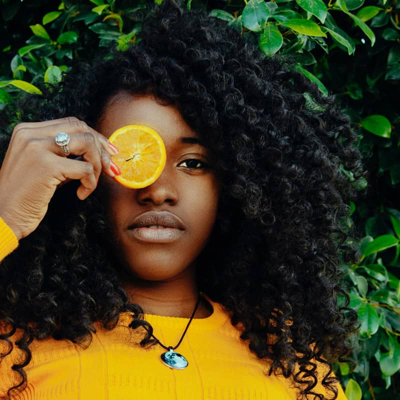 Woman with curly hair holding lemon